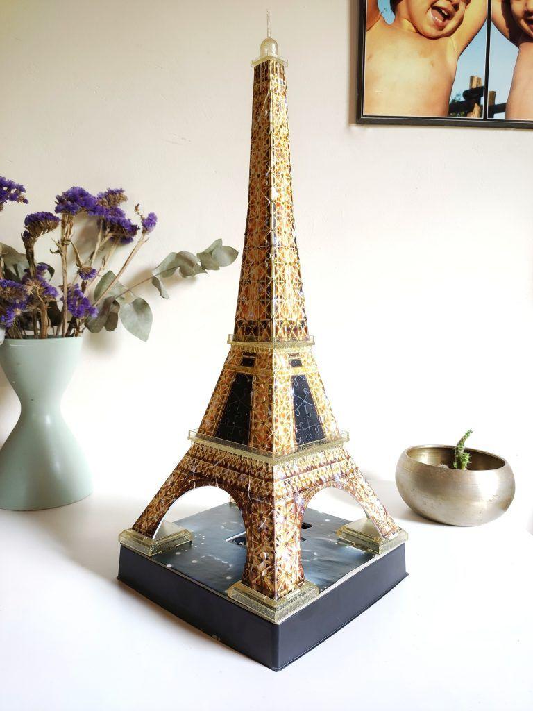 Puzzle en 3D de la Torre Eiffel. Está puesto en una mesa, al lado de un cuenco y de un jarrón con flores. El puzzle se ilumina.